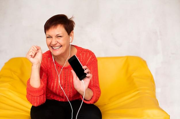 Happy senior female on couch listening music