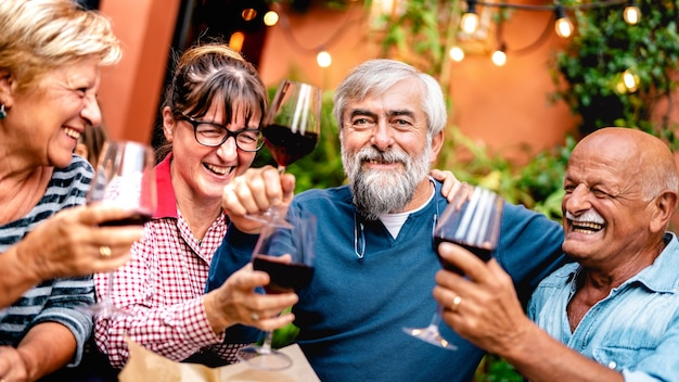 Happy senior friends having fun toasting red wine at dinner party - focus on bearded man