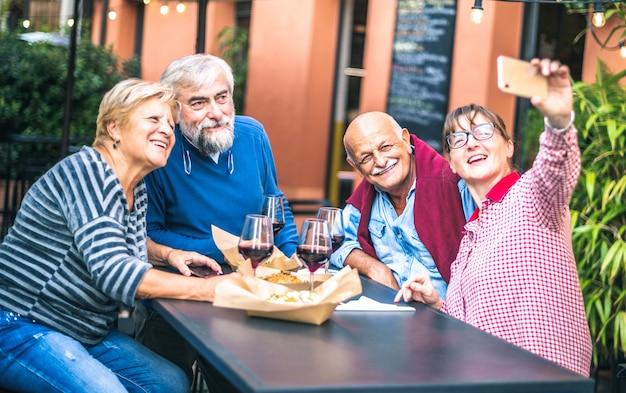 Счастливые старшие друзья, делающие селфи в ресторане