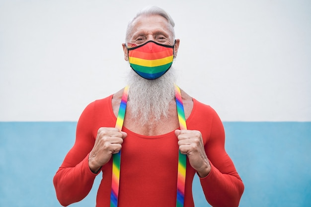 Счастливый старший гей мужчина в маске радужного флага на параде лгбт