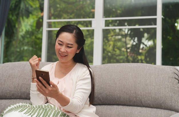 Happy senior glad looking stock market investment to success in smartphone at home
