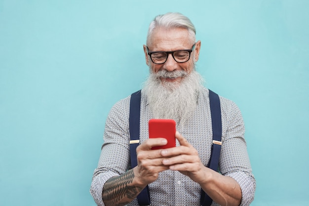Happy senior hipster man using mobile phone outdoors in the city Premium Photo