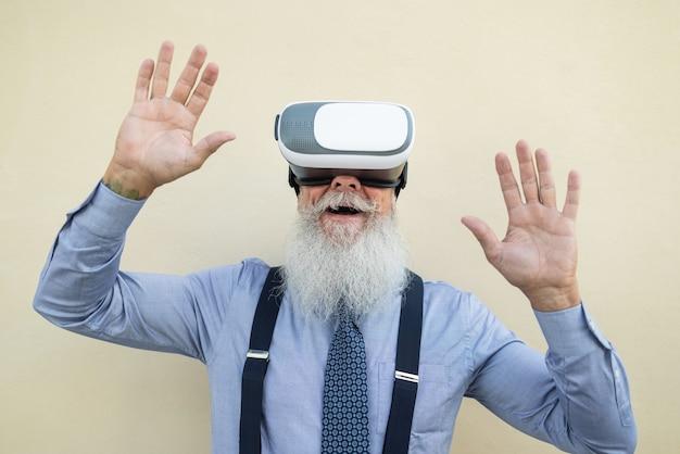 バーチャルリアリティヘッドセットを使用して幸せなシニアヒップスターの男-vrゴーグルに焦点を当てる