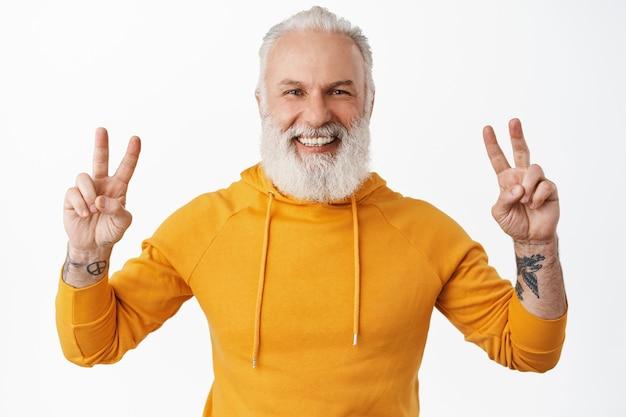 Felice hipster senior con tatuaggi che mostrano il segno della pace v e sorridente, ridendo felice mentre indossa una felpa con cappuccio moderna arancione e si diverte, in piedi sul muro bianco