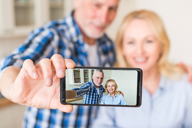 Happy senior husband and wife are making selfie on mobile phone in kitchen