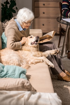 Happy senior lady cuddling with dog on couch