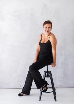 スツールに座って幸せなシニア女性