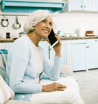 自宅で携帯電話を使用して幸せなシニア女性