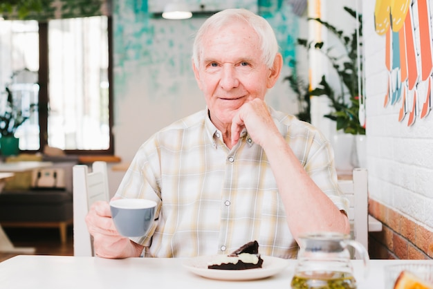 Happy senior male sitting in cafe enjoying tea and dessert