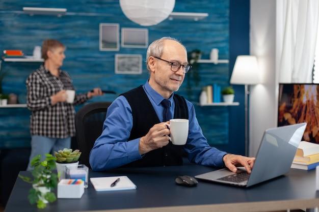 机に座って良いニュースのメールを読んだ後の幸せな年配の男性。妻がテレビのリモートを保持している間、机に座ってポータブルコンピュータを使用して自宅の職場で老人起業家。