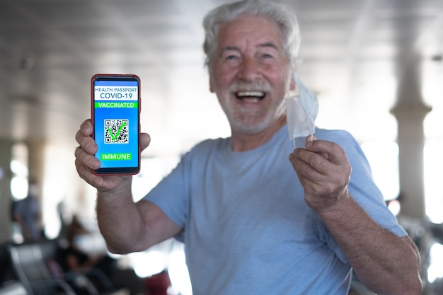 Happy senior man in airport waiting for boarding shows green pass passport on mobile phone for people vaccinated of covid-19, taking off the protective face mask