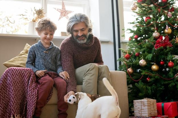 행복한 노인과 그의 귀여운 작은 손자는 크리스마스 이브에 창가에 장식된 전나무 옆 안락의자에 앉아 개와 놀고 있다