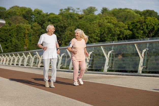 Счастливый старший мужчина и женщина вместе бегают по пешеходному мосту летом