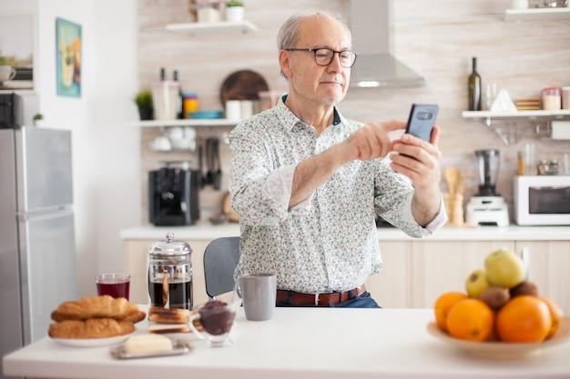 キッチンで朝食時にスマートフォンでインターネットを閲覧する幸せな年配の男性。インターネットオンラインチャット技術ビデオウェブカメラを使用してビデオ通話接続カメラ通信を行う高齢者