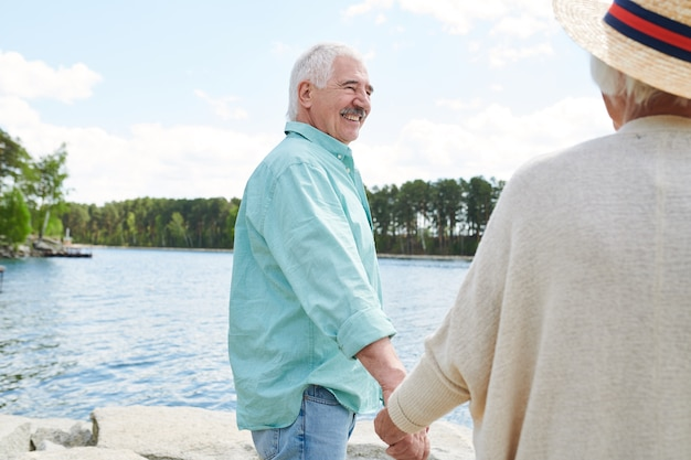 Happy senior man in casualwear holding his wife by hand while both spending weekend by lake in the country