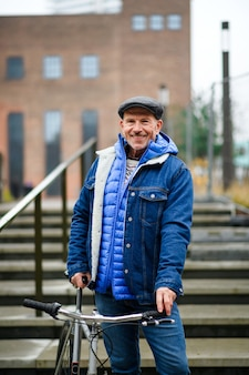 Happy senior man commuter with bicycle outdoors in city, looking at camera.