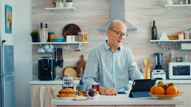 Happy senior man during breakfast in kitchen having a video conference with family. elderly person using internet online chat technology video webcam making a video call connection camera communicatio