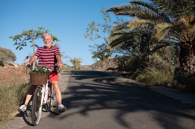 빈티지 자전거와 함께 야외에서 즐기는 행복 한 노인. 흰 머리를 하고 웃고 있는 한 사람. 식물과 식물의 배경입니다. 파란 하늘