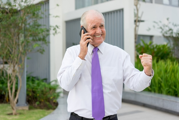 Happy senior man in formalwear talking on mobile phone and making winning gesture
