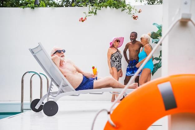 Happy senior man having party in the swimming pool