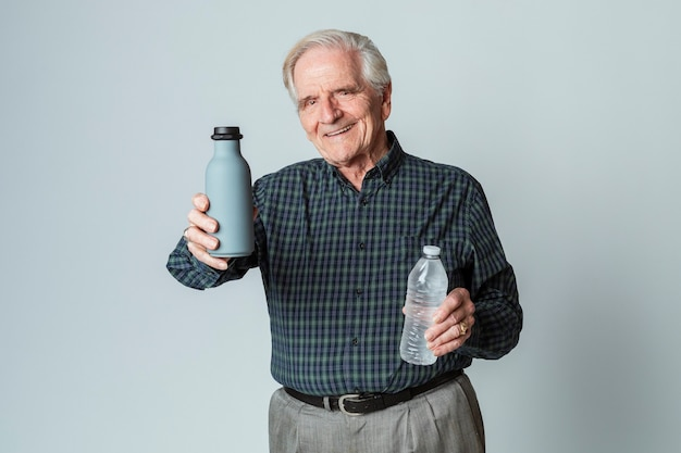 재사용 가능한 플라스틱 물병을 들고 있는 행복한 노인