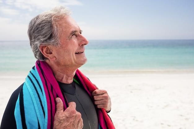 Счастливый старший мужчина держит полотенце вокруг его шеи