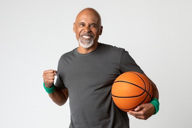 Happy senior man holding a basketball