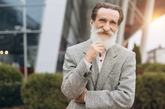 Happy senior man holding his grey bearded on the office buildings with copy space