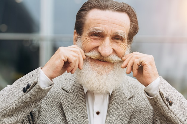 Happy senior man holding his mustache on the office buildings