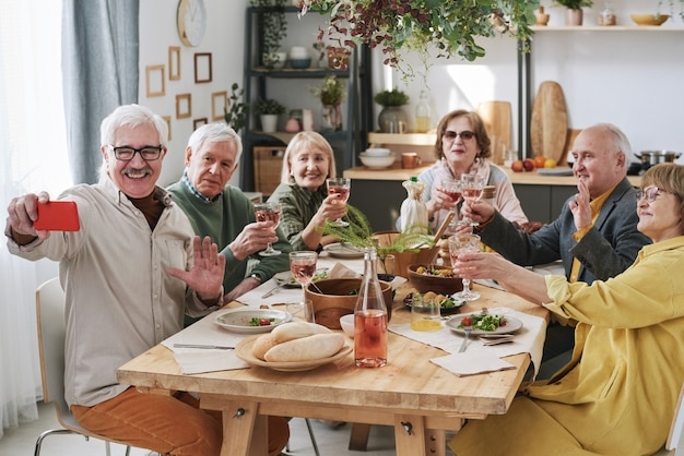Happy senior man holding mobile phone and making a photo with his old friends during dinner at the table