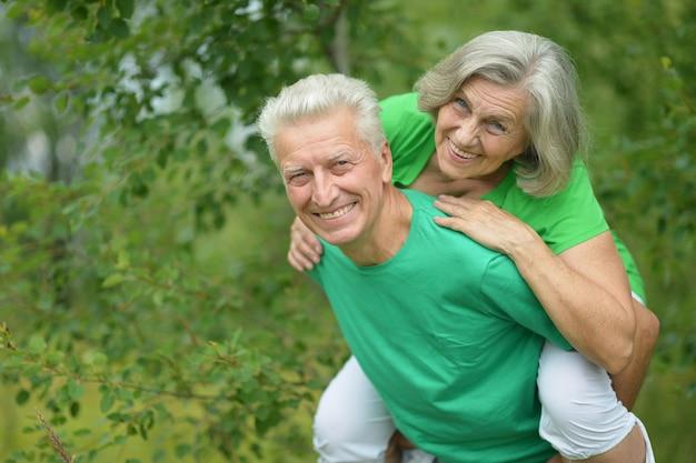 Happy senior man hugging senior woman in summer forest