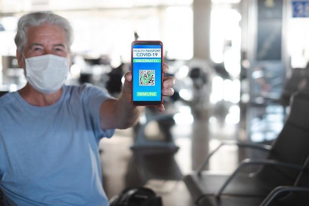 搭乗を待っている空港で幸せな年配の男性は、covid-19のワクチン接種を受けた人々のために携帯電話でグリーンパスパスポートを示しています