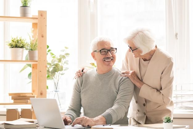Счастливый старший мужчина в повседневной одежде сидит за столом перед ноутбуком, разговаривая со своей женой, стоящей рядом с ним