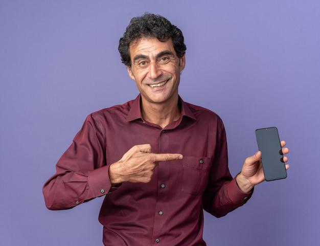 人差し指で元気に笑ってスマートフォンを指している紫色のシャツを着た幸せな年配の男性