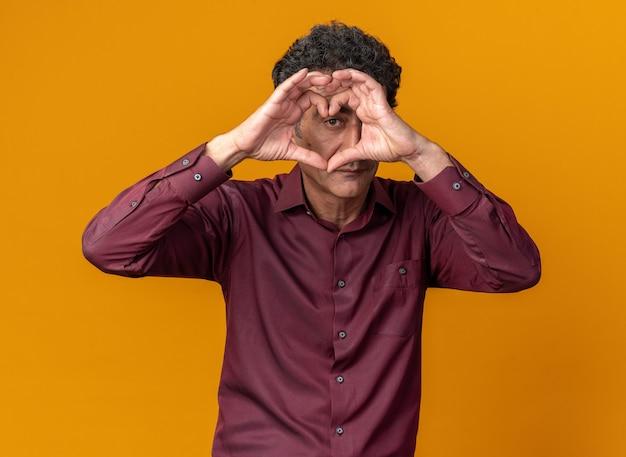 オレンジ色の背景の上に立ってハートジェスチャーを作る指を通して見ている紫色のシャツの幸せな年配の男性