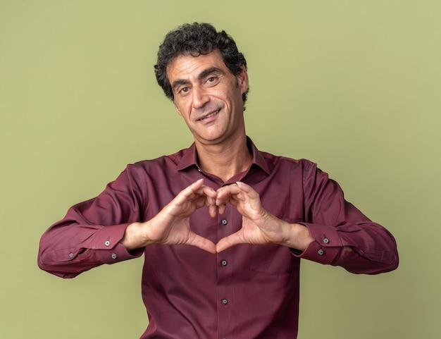 緑の背景の上に元気に立って笑顔の指でハートジェスチャーを作る紫色のシャツの幸せな年配の男性