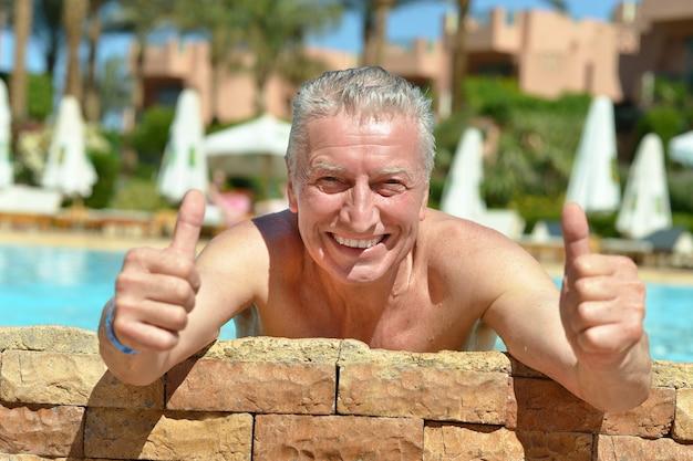 엄지손가락으로 수영장에서 행복 한 수석 남자