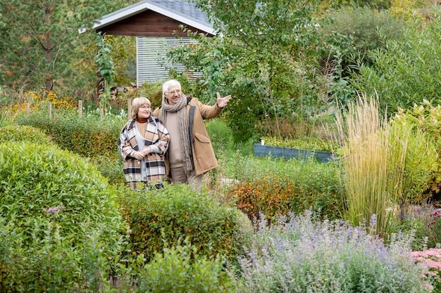 덤불과 나무 사이에서 아내와 이야기하면서 정원에서 자라는 녹색 식물을 가리키는 따뜻한 캐주얼웨어를 입은 행복한 노인