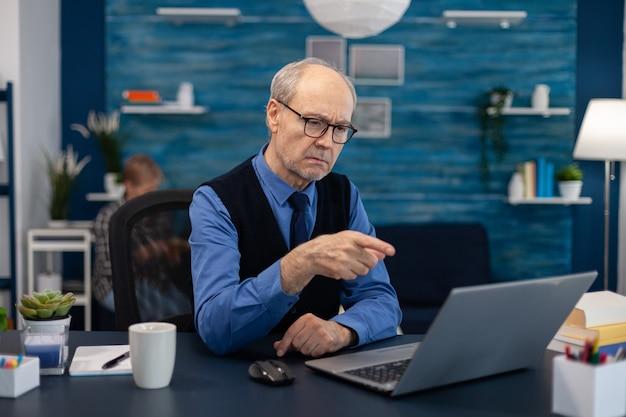 ビデオ会議中にラップトップを指して幸せな年配の男性。机に座ってチャットしながらノートパソコンのウェブカメラで笑っている白髪の陽気な年金受給者。