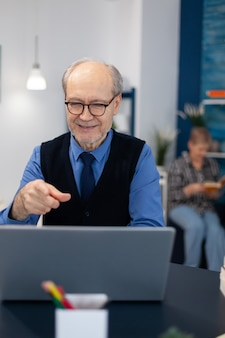 Happy senior man pointing at laptop during video conference