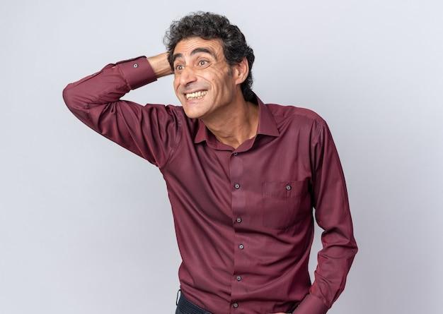 Felice uomo anziano in camicia viola che guarda da parte stupito e sorpreso con la mano sulla testa in piedi su sfondo bianco