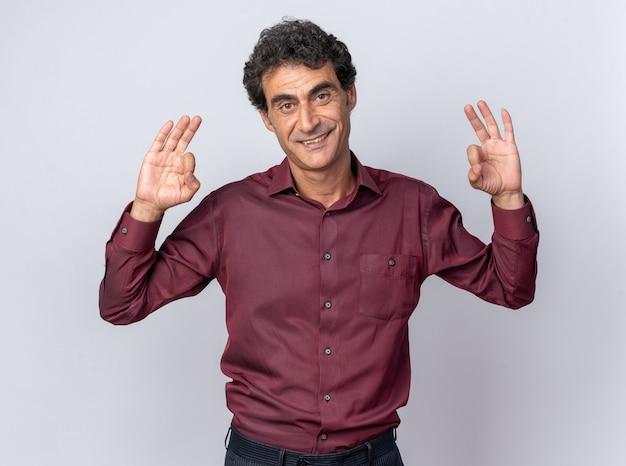 Uomo anziano felice in camicia viola che guarda l'obbiettivo sorridente fiducioso mostrando segno ok