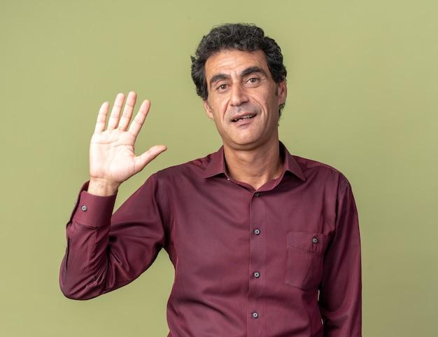Felice uomo anziano in camicia viola che guarda la telecamera sorridente amichevole che saluta con la mano in piedi su sfondo verde