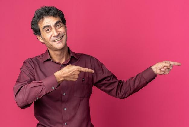 Felice uomo anziano in camicia viola che guarda la telecamera sorridente che punta con il dito indice a lato in piedi su sfondo rosa