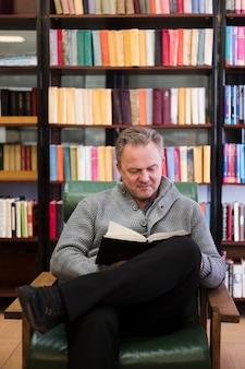 Счастливый старший мужчина читает книгу