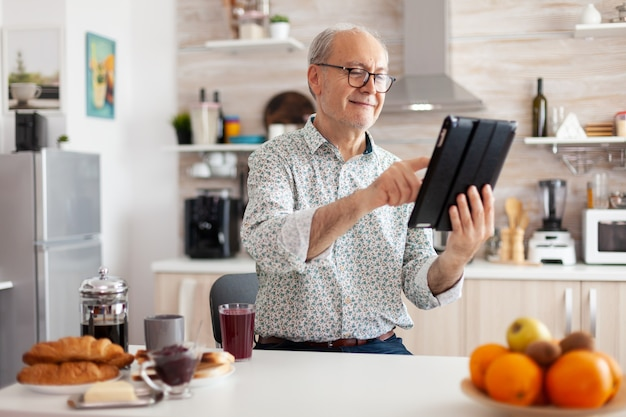 Happy senior man searching on tablet in kitchen during breakfast enjoying loisire time. elderly retired person working from home, telecommuting using remote internet job online communication.