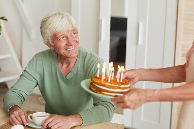 彼の妻が自宅で彼にバースデーケーキを提供している間、テーブルに座っている幸せな年配の男性