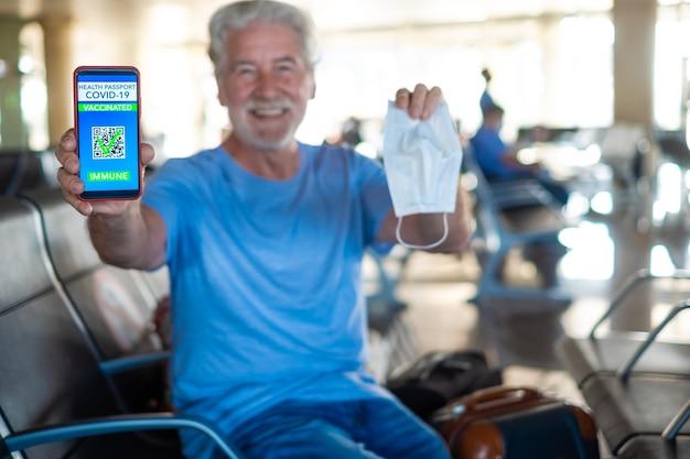 搭乗を待っている空港に座っている幸せな年配の男性は、covid-19のワクチン接種を受けた人々のために携帯電話でグリーンパスパスポートを示しています