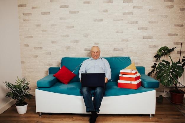 집에서 파란색 소파에 앉아 행복 수석 남자와 노트북을 사용하고 있습니다. 온라인 원격 작업. 홈 오피스에서 수석 사업가입니다.