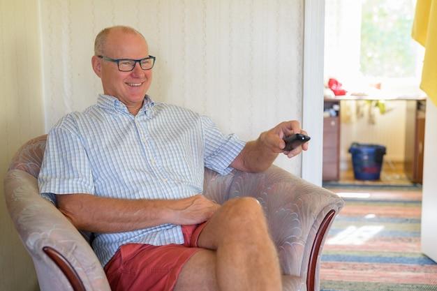 家でテレビを見ながら座っている幸せな年配の男性